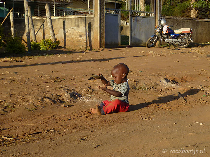 Uganda, Boy Playing With Sand.