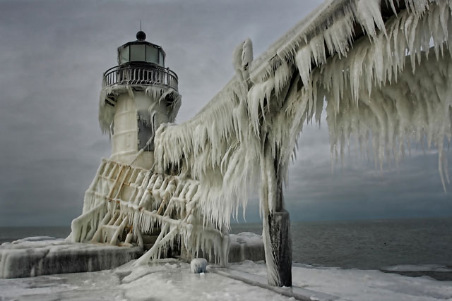 Frozen Lighthouses Caught In Winter's Icy Grip On Lake Michigan Shore