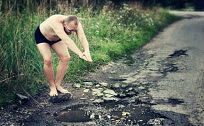 Friends Take Funny Pothole Photos To Draw Government's Attention To Poor Road Conditions In Kaunas