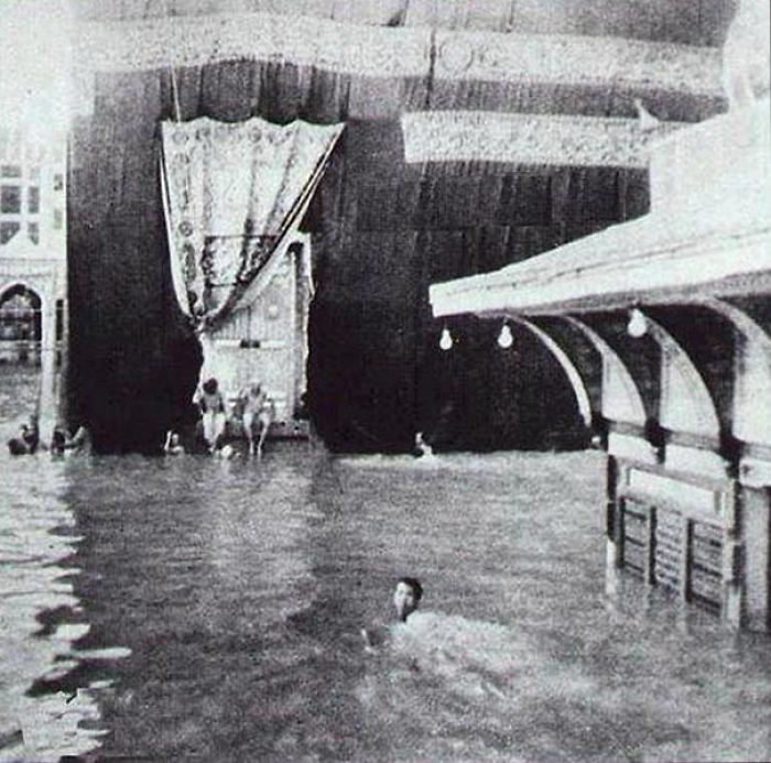 People Swimming Around The Kaaba, The Holy Place Of The Muslims, After A Heavy Rain.