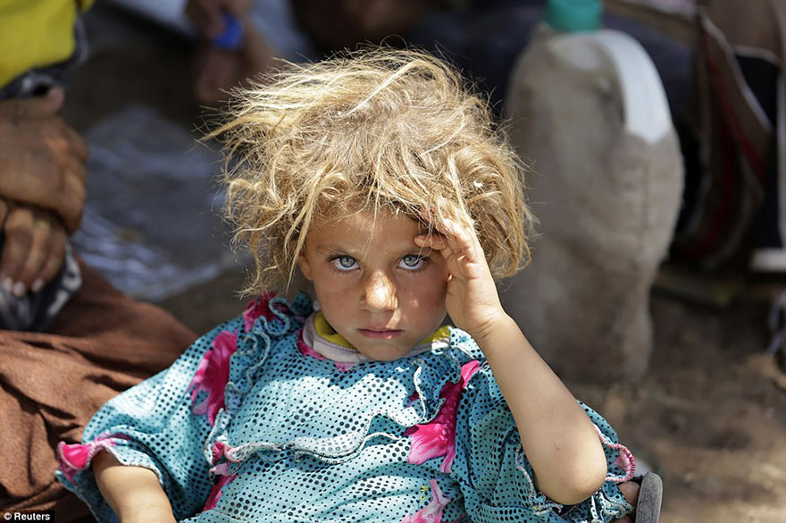 A Girl From The Minority Yazidi Sect Rests At The Iraqi-Syrian Border