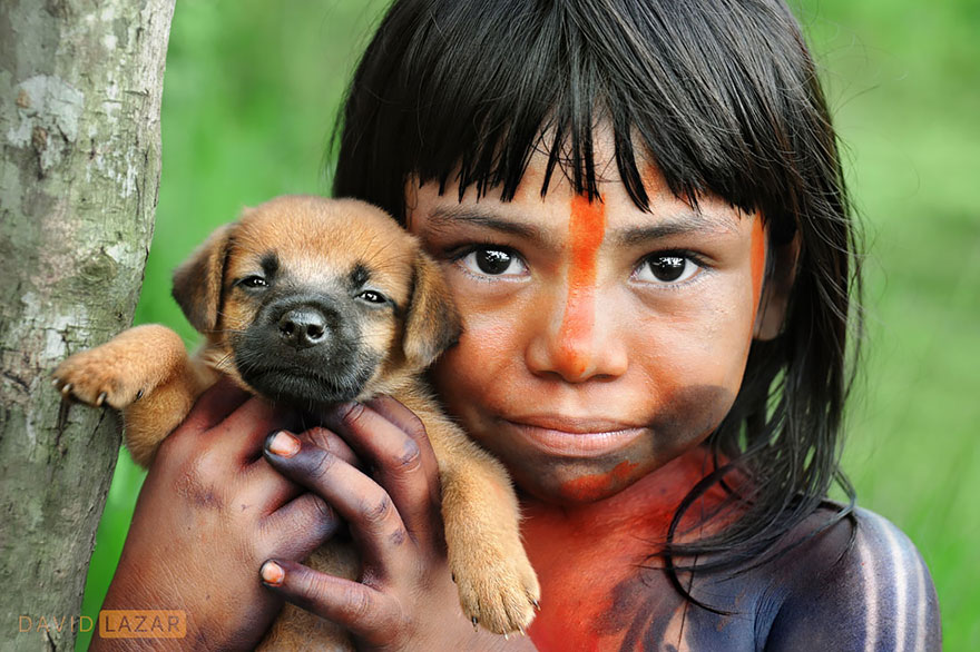A Girl Covered In Traditional Body Paint Holds Her Puppy
