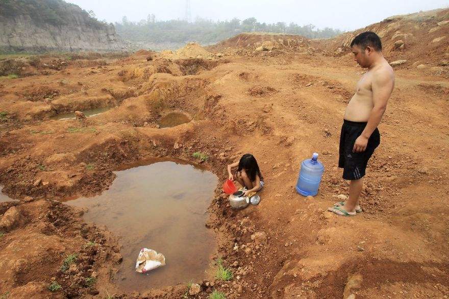 girl collects water from a puddle at a dried-up reservoir as her father stands beside her in Baofeng county