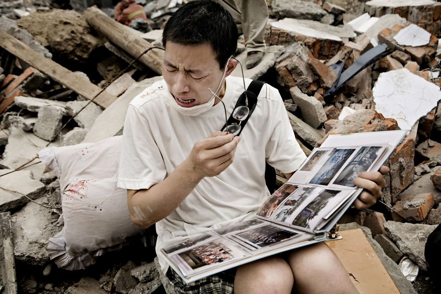 A Man Cries While Flipping Through A Family Album He Found In The Rubble Of His Old House