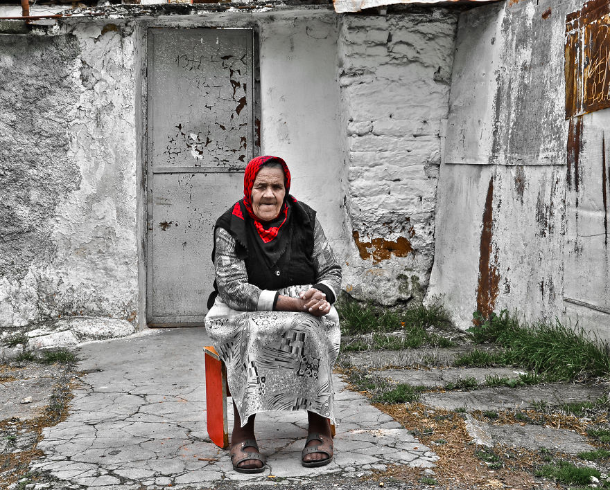 An Old Romani Woman Sitting In Front Of Her House In Tirana, Albania