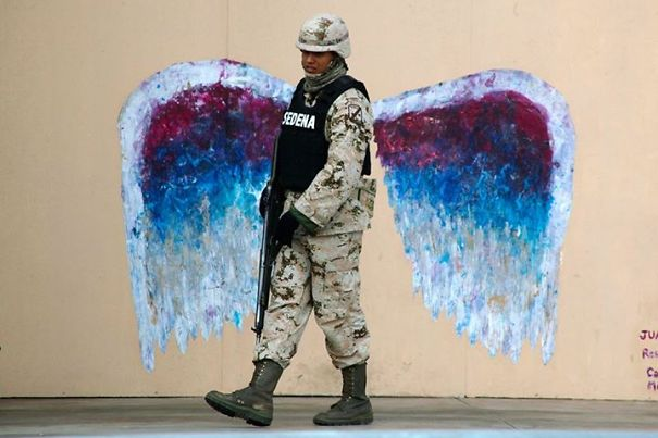 A Soldier Walks Past Graffiti Depicting Angel Wings
