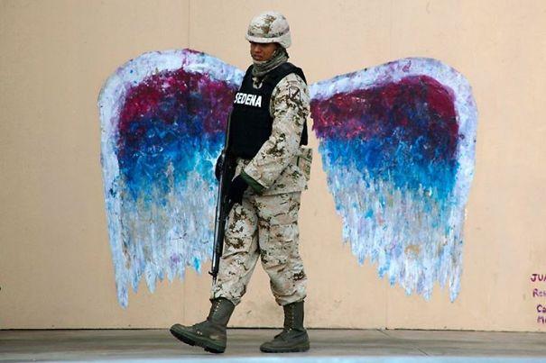 A Soldier Walks Past Graffiti Depicting Angel Wings