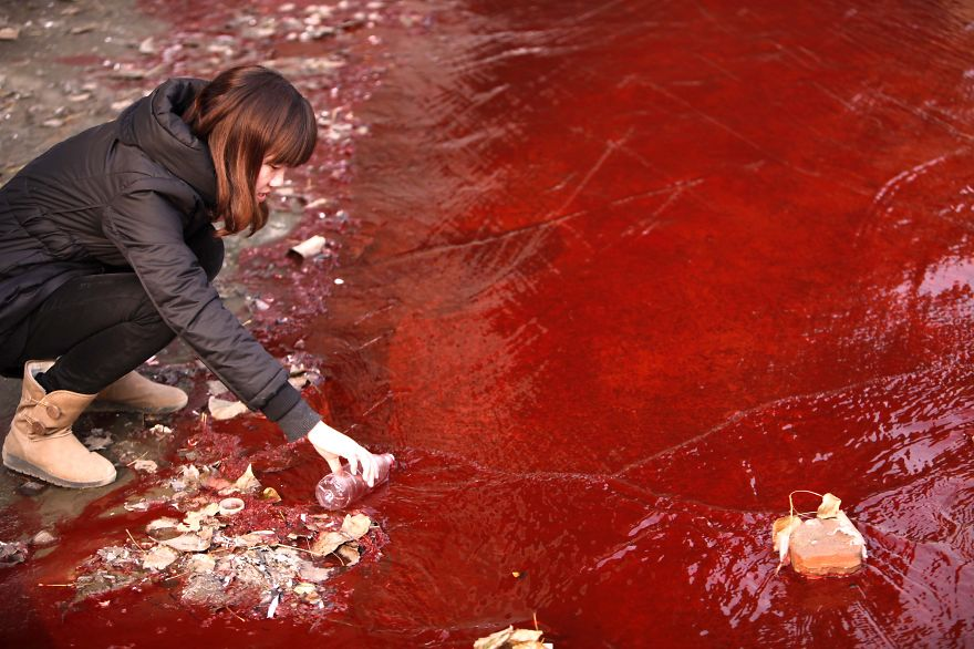 Journalist Takes A Sample Of Polluted Red Water From Jianhe River