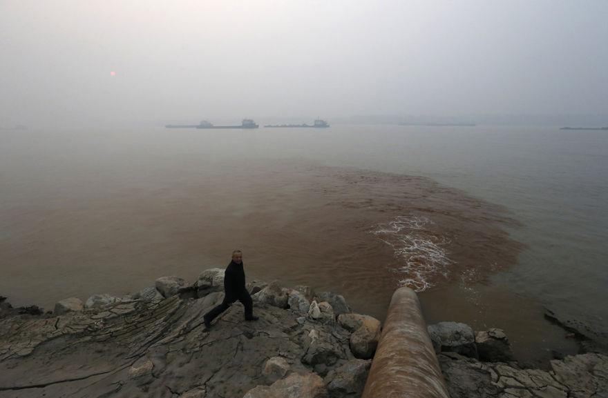Man Walks By Pipe Discharging Waste Water Into Yangtze River