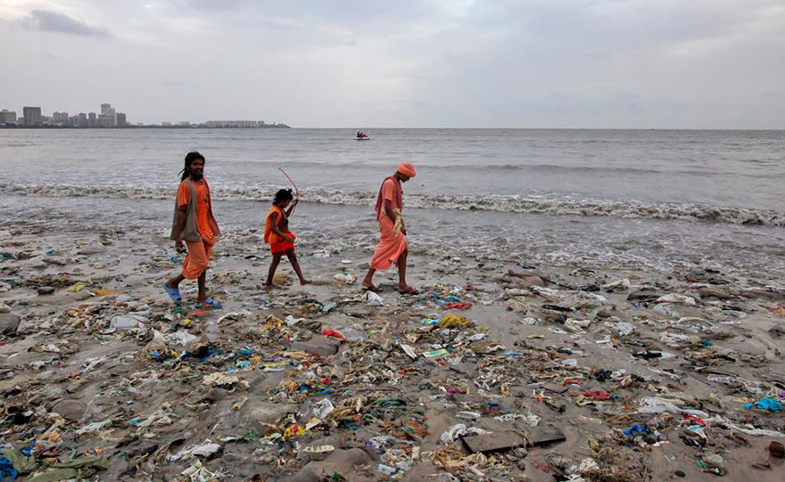 A Family Walks On A Garbage-strewn Beach In Mumbai