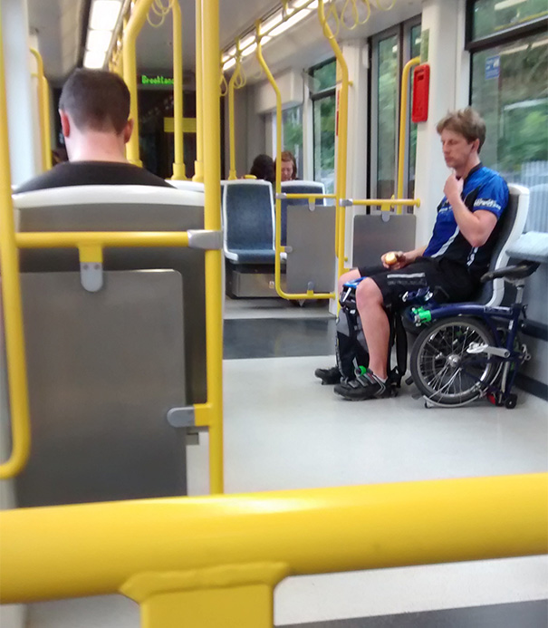This Guys Folded Bicycle Makes Him Look Like He's Sitting In A Wheel Chair Whilst On The Tram