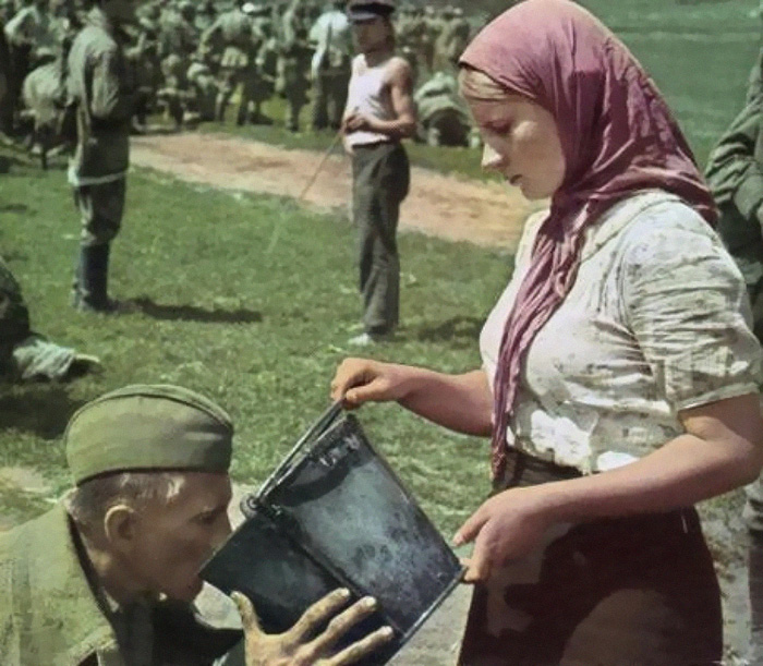 Soviet Soldier Is Given Water By A Ukrainian Woman After Being Captured During The Battle For Kiev (1941)
