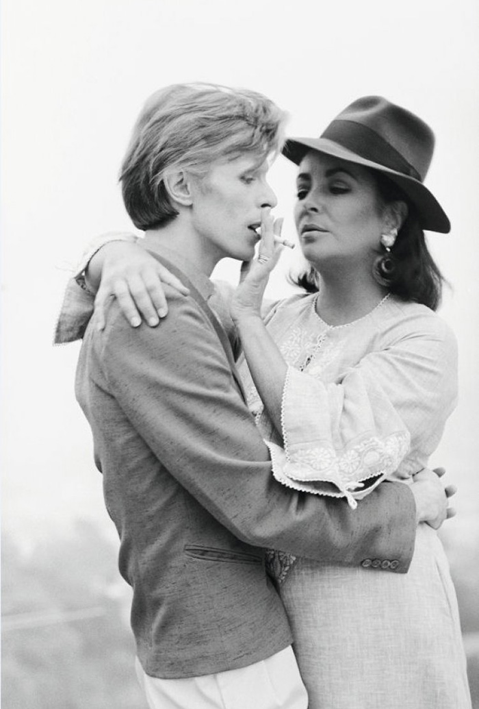 Singer David Bowie Sharing A Cigarette With Actress Elizabeth Taylor In Beverly Hills (1975)