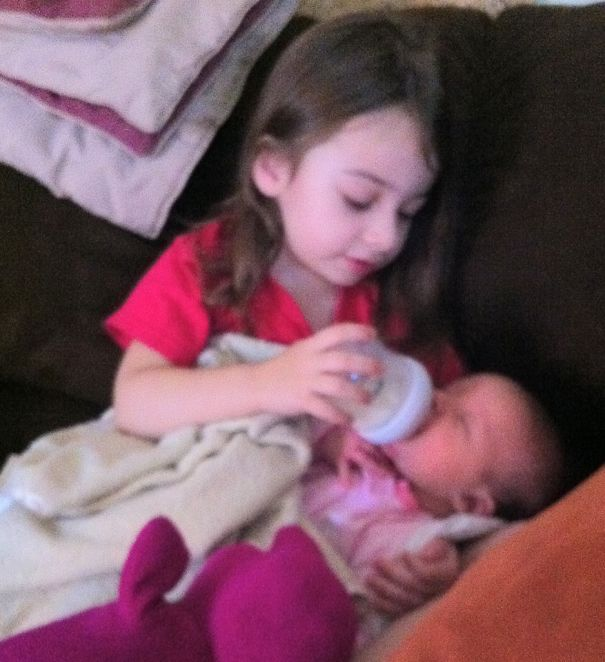 My 3-year Old Daughter Feeding Her Newborn Sister.