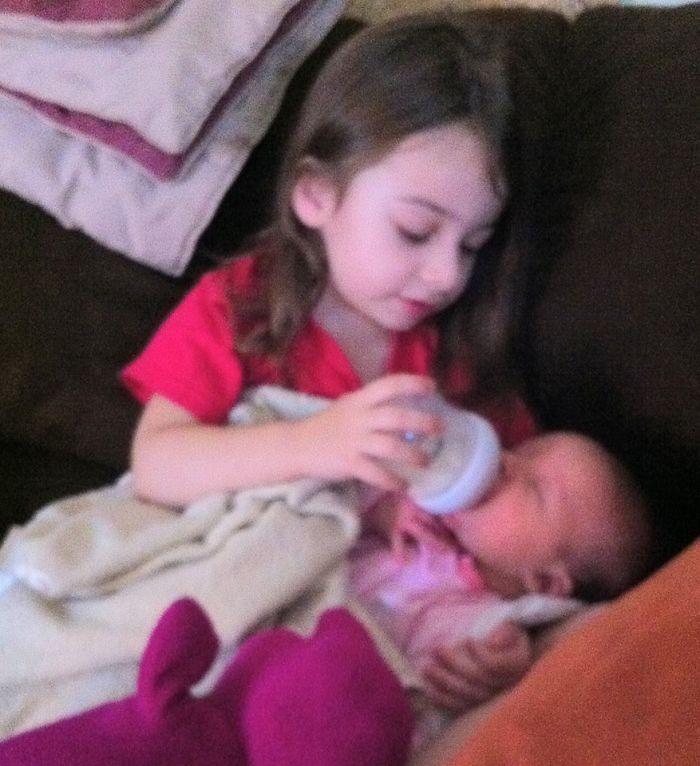 My 3-year Old Daughter Feeding Her Newborn Sister.