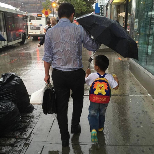 Soaked Dad Protecting His Schoolboy From Rain Shows What Parenting Is