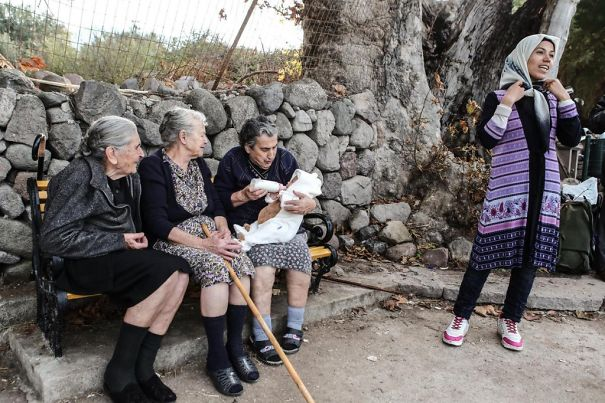 3 Old Greek Ladies In Lesvos, Feed, Sooth And Sing To Crying Refugee Baby, While Mother Smiles
