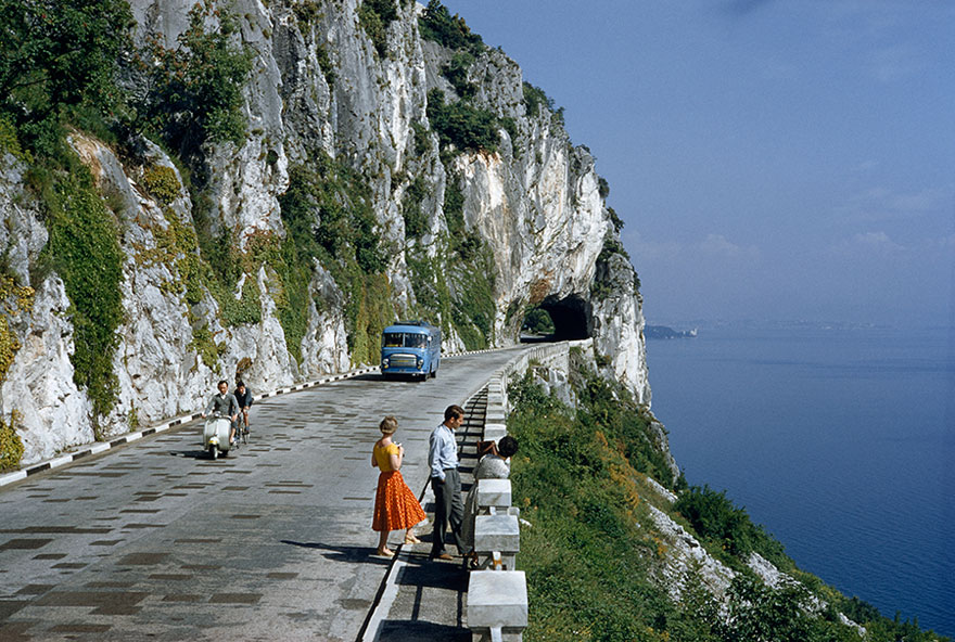 Motorists Pass People On A Scenic Road Atop A Cliff Overlooking A Bay Near Trieste, Italy, 1956