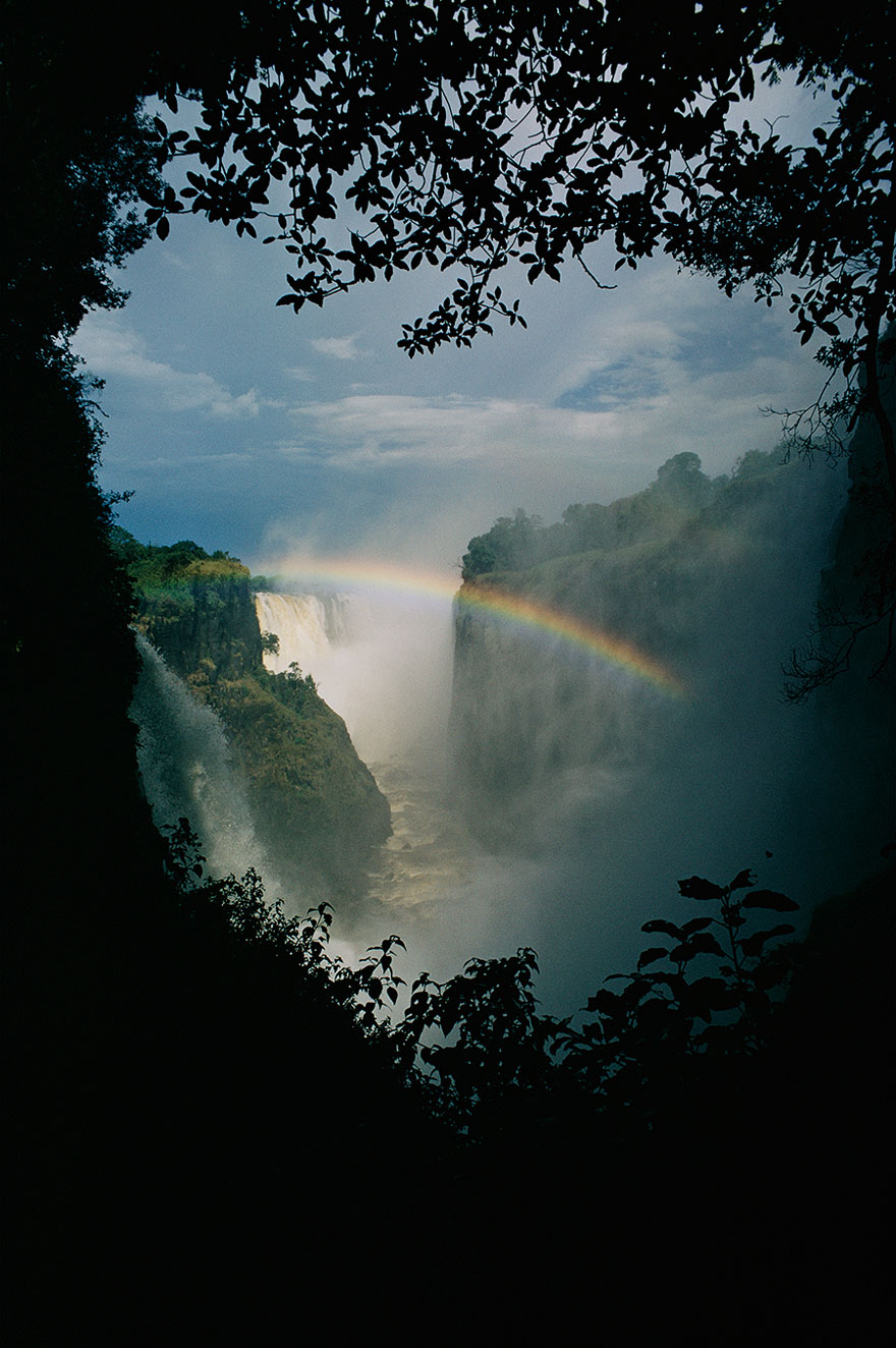 A Rainbow Arches Over Victoria Falls In Zimbabwe