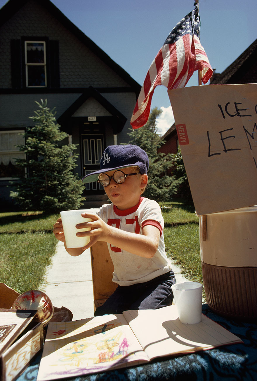 A Boy Sells Lemonade From His Front Yard Stand On Main Street In Aspen, Colorado, 1973