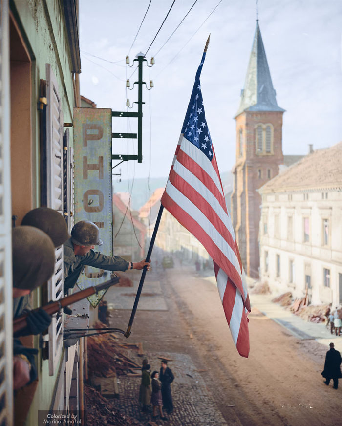 Captain Thomas H. Garahan Raises The 'stars And Stripes' Flag Made Secretly By A Local French Girl, 1945.