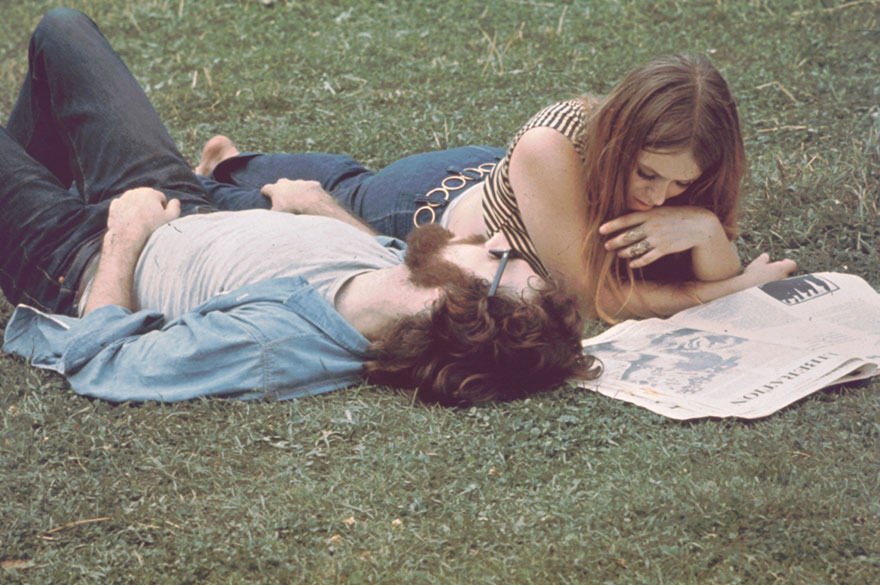 A Young Woman Lies On Grass And Reads Newspaper, A Young Man Beside Her, During The Woodstock Music And Arts Fair