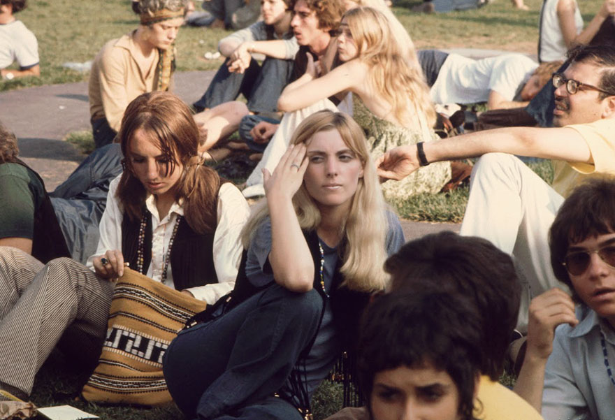Women Sit On The Grass And Wait For A Bus To Take Them To The Woodstock Music And Arts Fair