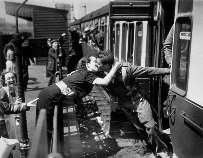 A Woman Leans Over The Railing To Kiss A British Soldier Returning From World War II, London, 1940