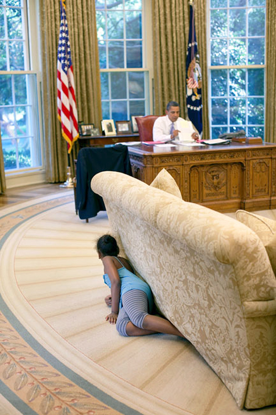 President Barack Obama's Daughter Sasha Hides Behind The Sofa As She Sneaks Up On Him At The End Of The Day In The Oval Office