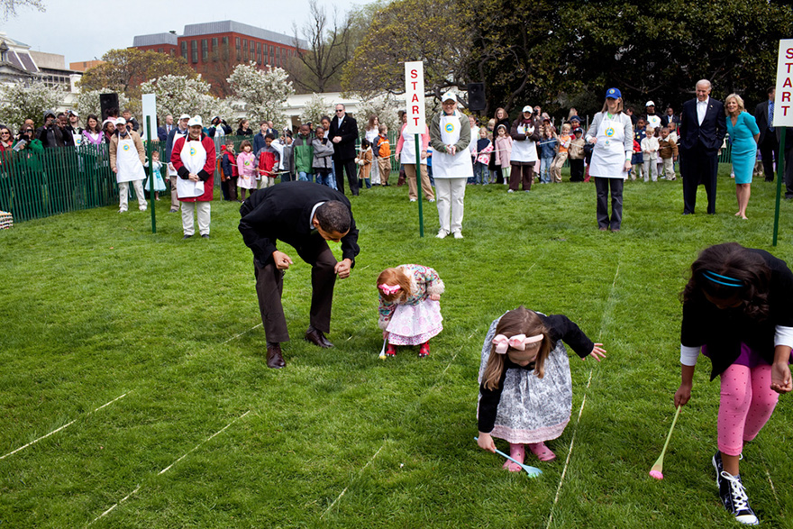 President Barack Obama Cheers On A Young Child As She Rolls Her Egg Toward The Finish Line During The White House Easter Egg Roll