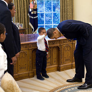 A Young Boy Reaches Up To Compare The President's Hair To His Own