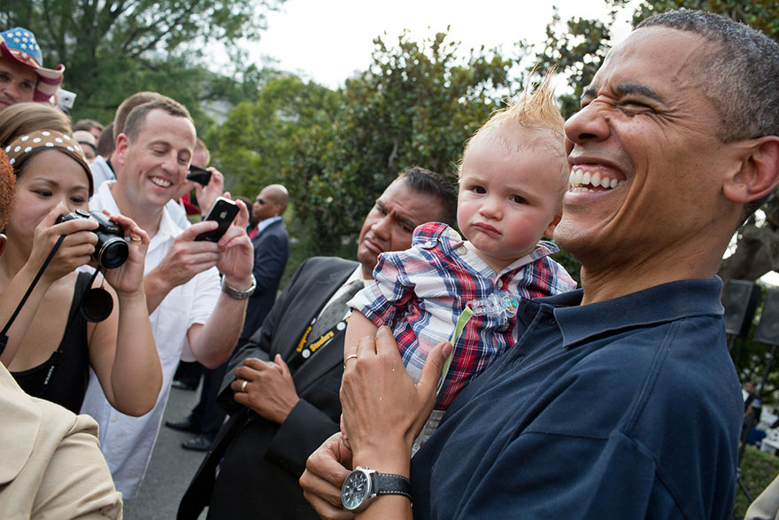 President Barack Obama Holds A Baby While Greeting Guests During An Independence Day Celebration