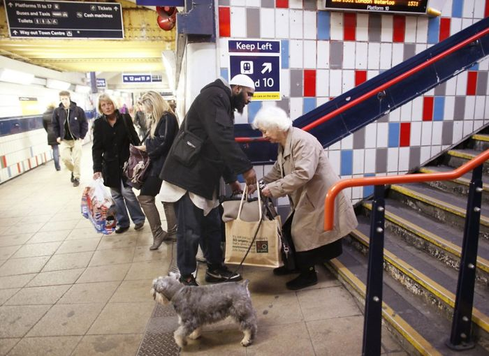 A Guy Helping An Old Woman Carry Her Stuff