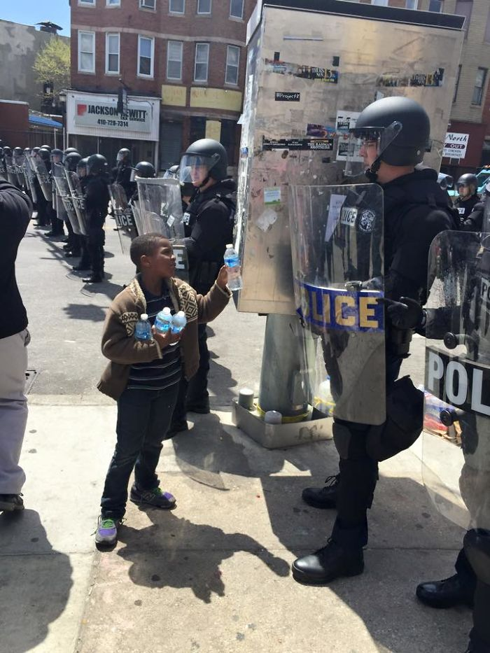 A Boy Giving Water To The Officers