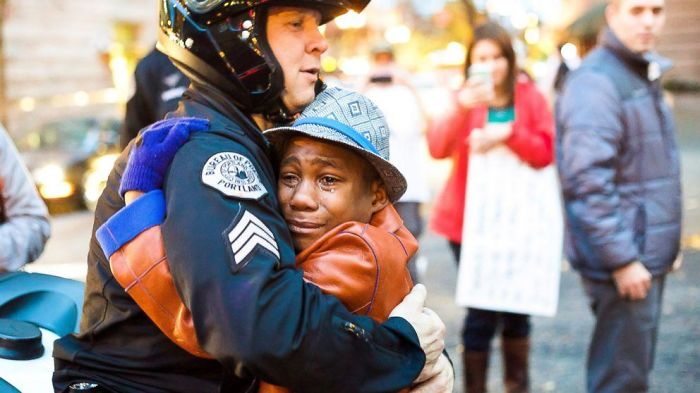 Officer And Crying Boy Hugging