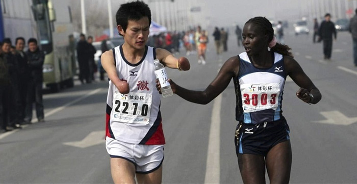 Woman Handing A Bottle Of Water To A Fellow Runner Without Hands