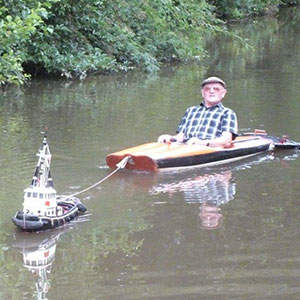 Man Spotted Using Tiny Tug Boat To Effortlessly Cruise Down The River
