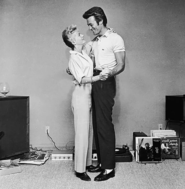 Clint Eastwood And His First Wife, Maggie, Dancing Next To A Turntable And A Rack Full Of Records In A Living Room In The 60's