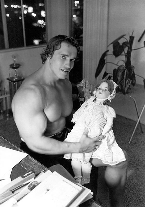 Young Arnold Schwarzenegger Holding A Doll In The 70's