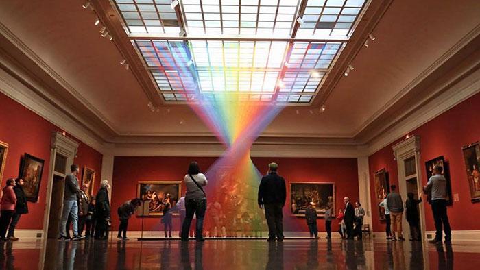 Este arco iris artificial atrapado en una galería de arte está hecho con miles de hilos de colores
