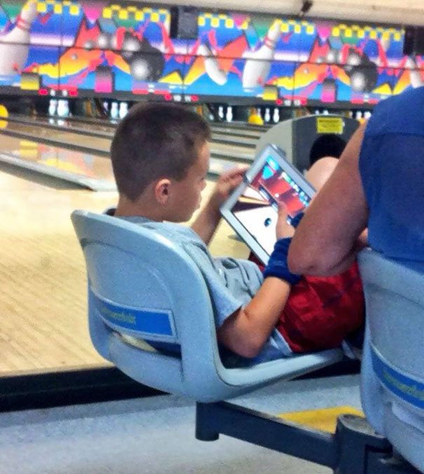 This Kid Is Playing A Bowling Game At A Bowling Alley