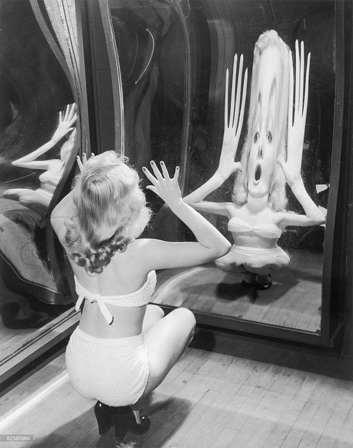 A Woman In A Toweling Bikini Poses In A Funfair Hall Of Mirrors, Circa 1935