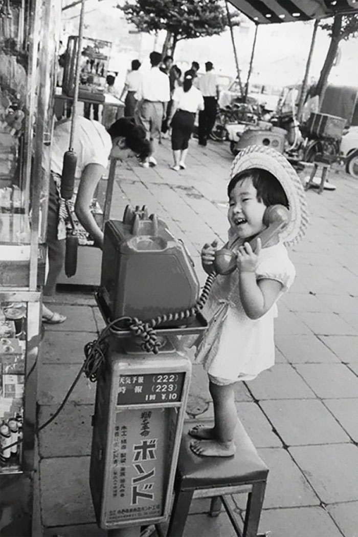 A Little Girl Having Fun Pretending To Talk On The Telephone, Japan, 1958