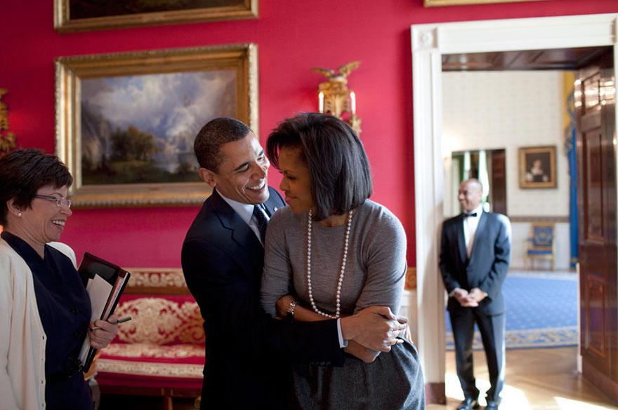 President Barack Obama Hugs First Lady Michelle Obama In The Red Room While Senior Advisor Valerie Jarrett Smiles At The White House On March 20, 2009