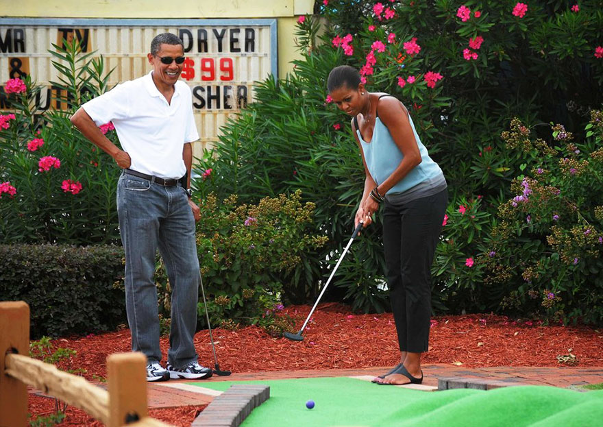 President Barack Obama Watches As First Lady Michelle Obama Putts During A Round Of Mini Golf At Pirate's Island Golf On Aug. 14, 2010 In Panama City Beach, Florida