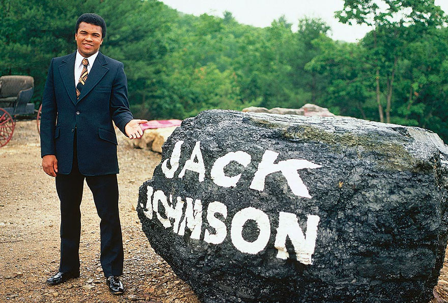 Muhammad Ali Is Photographed Next To A Boulder Paying Tribute To Legendary Boxer Jack Johnson At His Deer Lake, Pa Training Camp In July Of 1974
