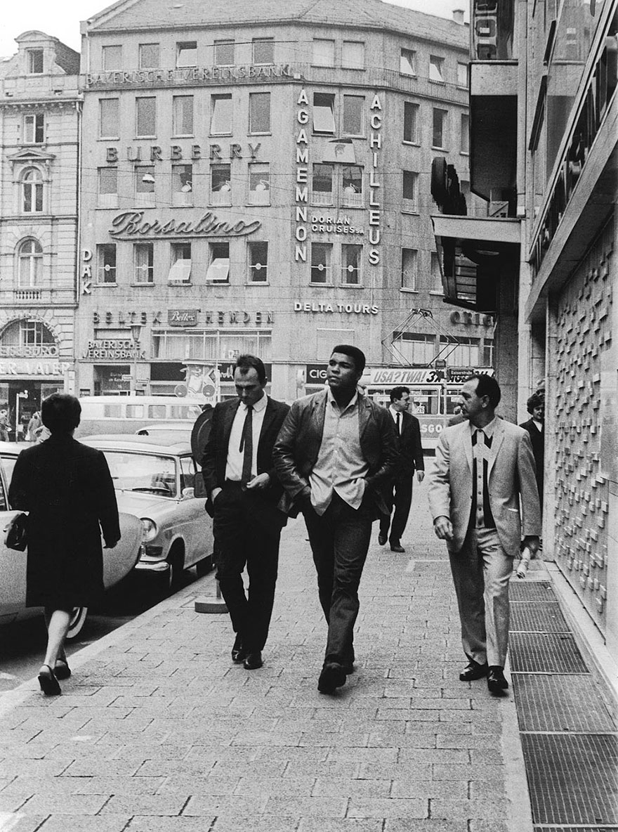 Muhammad Ali Walks Down A Main Street In Frankfurt, Germany With Boxing Promoter And Cornerman Angelo Dundee, While A Local Newsman Attempts To Get An Interview With The Prized Fighter, 1966