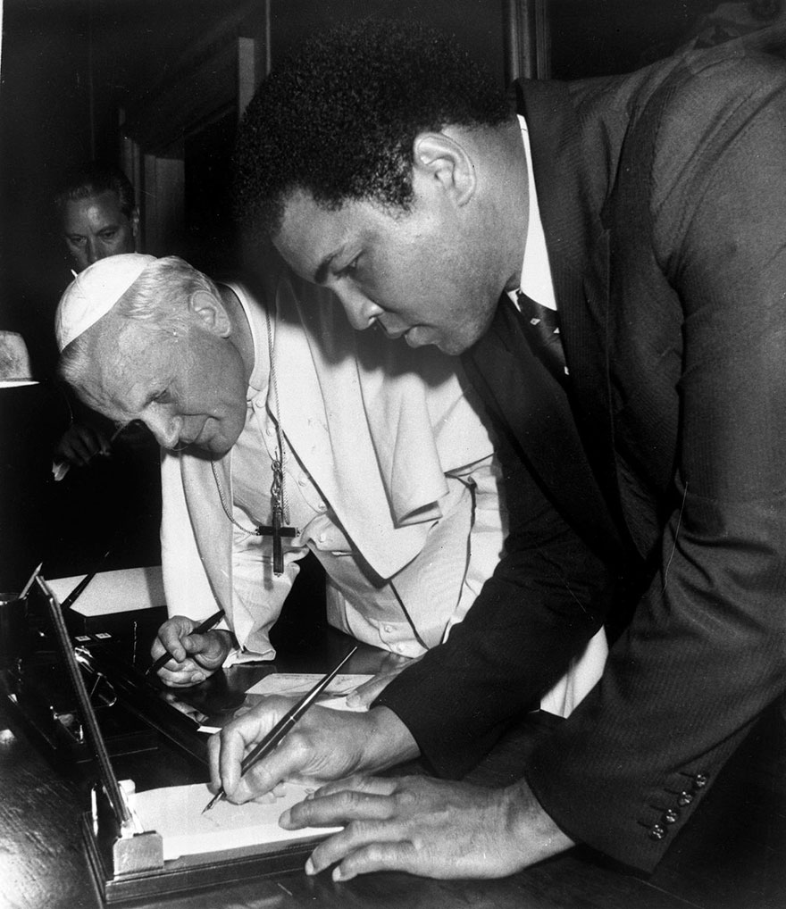 Pope John Paul II looks on as Muhammad Ali, former heavyweight boxing champion, signs his autograph in Vatican City, June 6, 1982