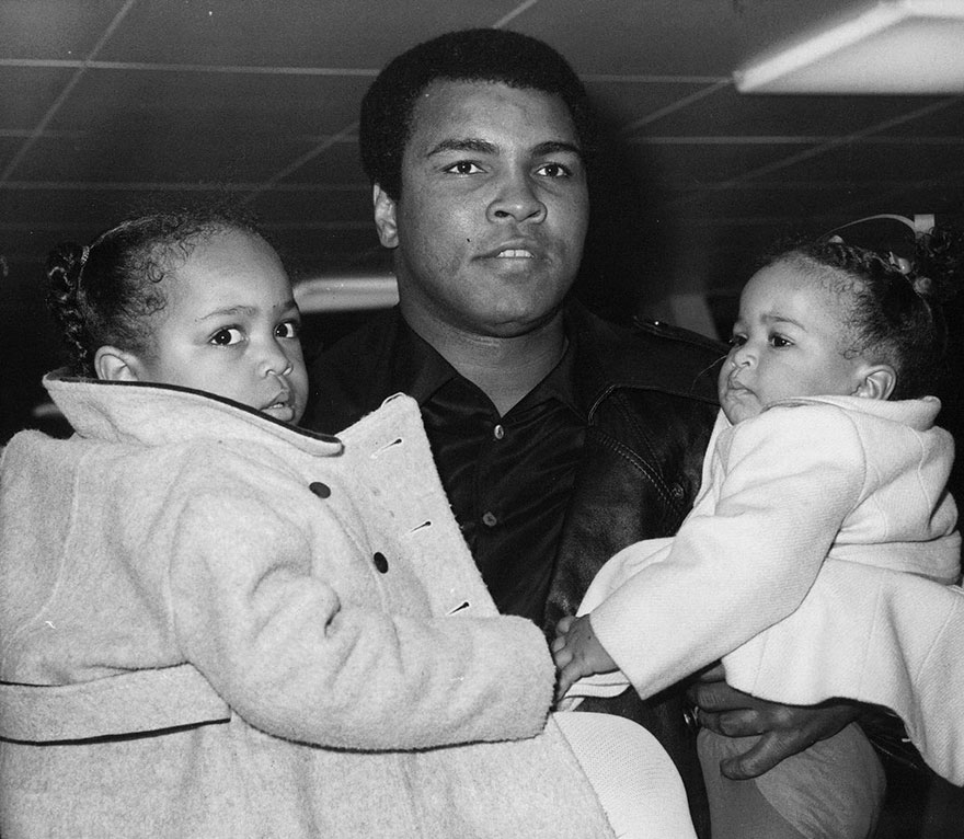 World heavyweight champion Muhammad Ali with both hands full at London's Heathrow Airport in 1977 when he left for New York with his daughters. Ali had been in Britain on a 2-day-visit to record a television sports interview
