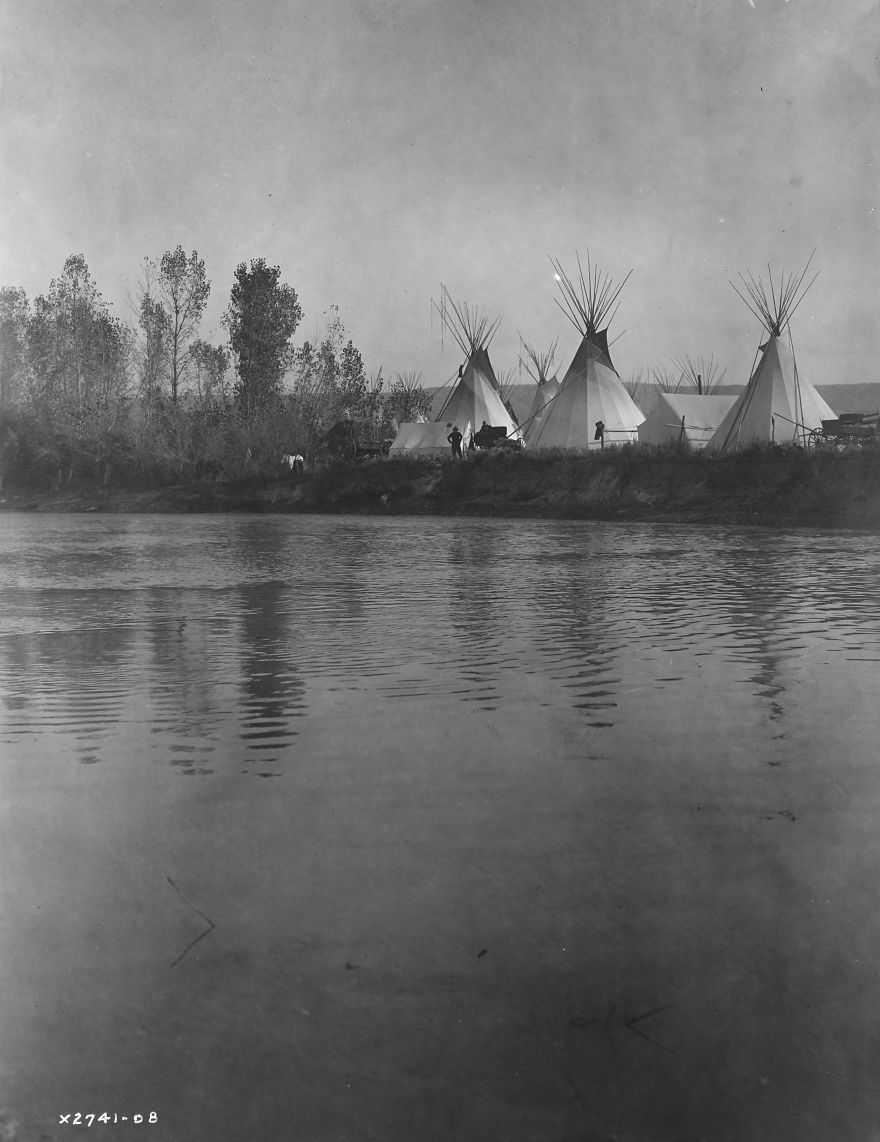 Crow Encampment With Tipis, Tents, Wagons, Horses And Men As Seen From The Distant Shore Of The River, 1908